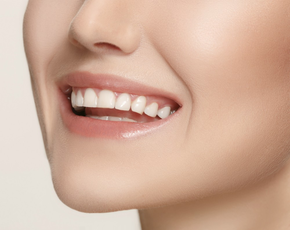 Beautiful and healthy woman smile, close-up on white background